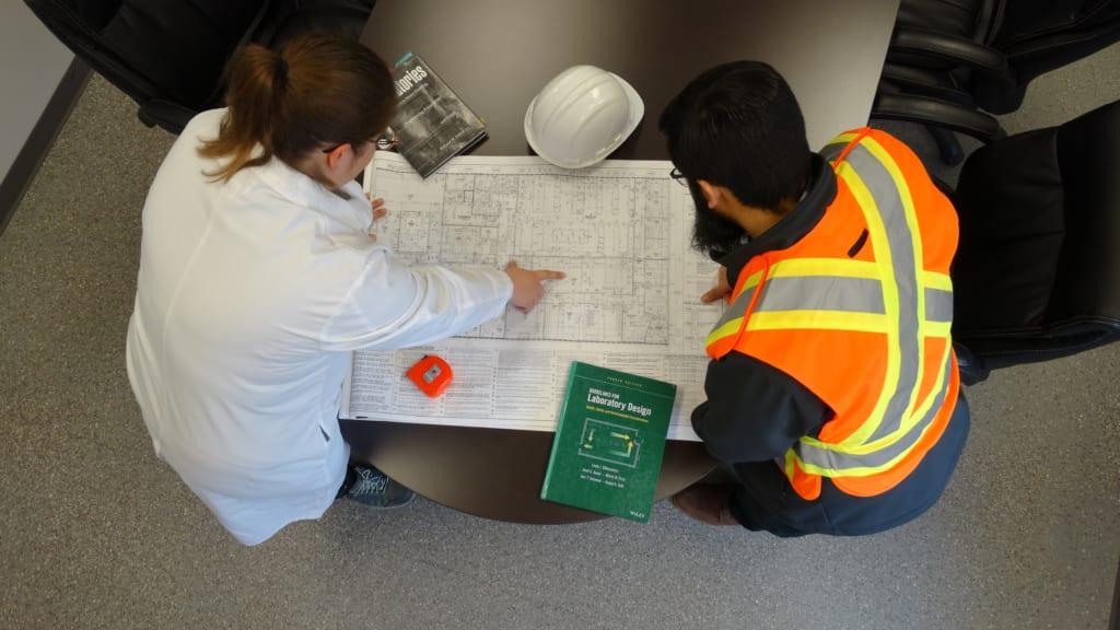 người quản lý phòng thí nghiệm xem xét các bản vẽ bố trí phòng thí nghiệm