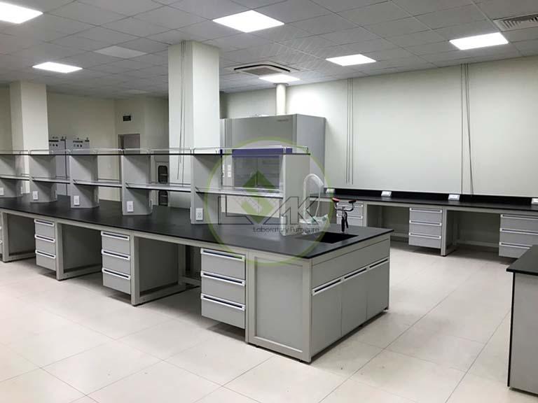 Bàn thí nghiệm trung tâm có kệ hóa chất 2 tầng phòng thí nghiệm nhà máy sản xuất dầu nhớt Công ty Maxihub